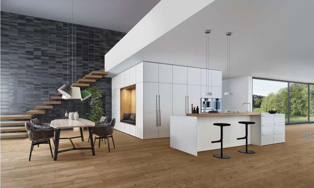 """Ein """"Raum im Raum"""" bildet das zentrale Element der von LEICHT entwickelten Küchenarchitektur. Das Konzept des begehbaren Raumes geht weit über die gängigen Planungsansätze hinaus. Der """"Raum im Raum"""" gegenüber der Insel erfüllt eine Vielzahl von Wohnraum- und Küchenfunktionen. So wird es möglich, die offene Küche noch wohnlicher zu gestalten. Der äußerst klaren Küchenarchitektur ent- spricht die ruhige Frontgestaltung: ein edler Mattlack in Schneeweiß. Foto: LEICHT"""