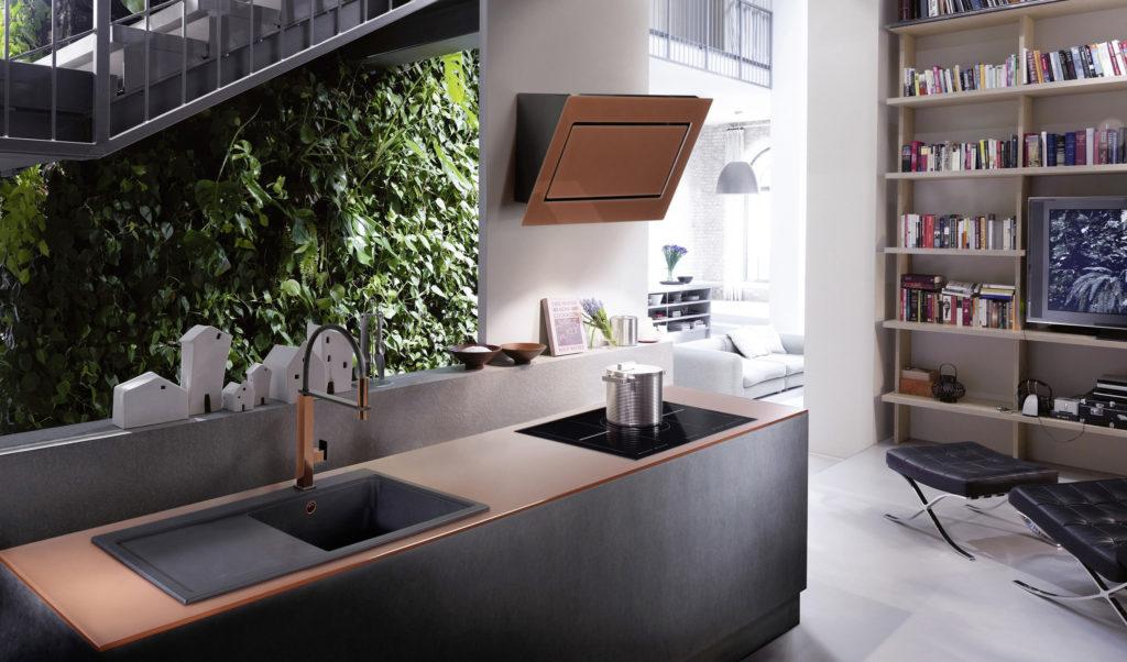 Angesagter Blickfang in dieser Küche ist die puristische Kopffreihaube mit einem Glasschirm in trendiger Kupfer-Optik. Die perfekte Ergänzung dazu: eine kupferfarbene Glasarbeitsplatte sowie eine Spüle und Arma-tur mit Kupfer-Elementen. (Foto: AMK)