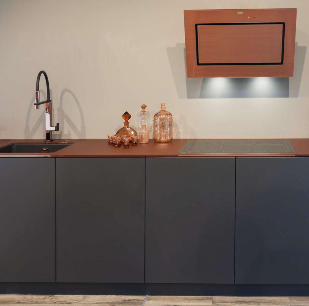 Die erfolgreiche Mythos Kopffreihaube wird mit der kupferfarben hinterdruckten Glasfront zum strahlenden Highlight der Küche. Drei Breiten bieten noch mehr Planungsflexibilität. Die LED-Spots befinden sich an der Haubenunterseite. Foto: Franke