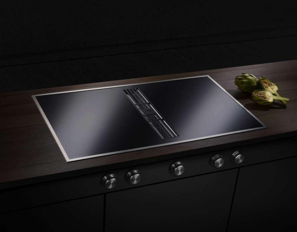 Von den Profis abgeschaut: Das neue Induktions-Kochfeld mit integrierter Muldenlüftung lässt sich über Edelstahl-Drehknebel bedienen. Foto: ©Küppersbusch