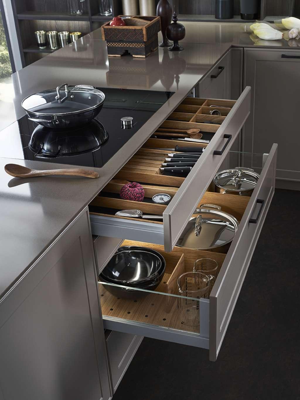 Das Innenausstattungssystem L-Box offenbart die hochwertige, funktionale Küchenplanung: Direkt unter dem Kochfeld befinden sich die Auszüge mit den am häufigsten benötigten Utensilien. Auch geöffnet sind Schubladen und Auszüge ansprechend gestaltet: Die Komponenten aus naturlackierter Eiche lassen sich variabel positionieren und sorgen für Ordnung. Foto: LEICHT