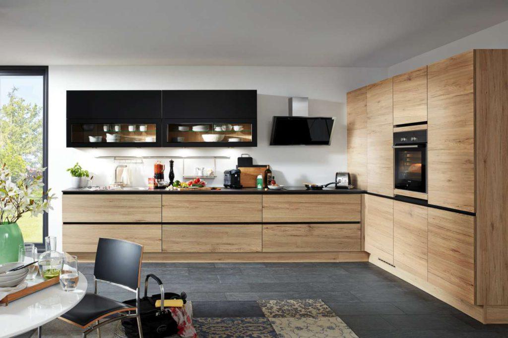 Für einen Wow-Effekt sorgen Holzfronten in Kombination mit einzelnen schwarzen Elementen. Foto: djd/KüchenTreff