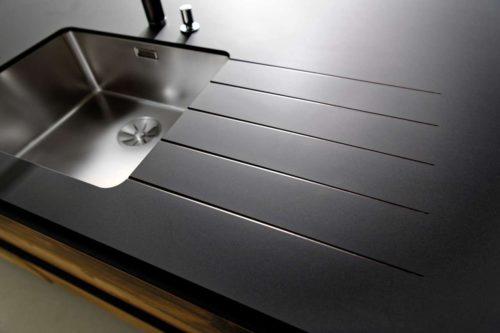 Der größte Feind der Küchenarbeitsplatten aus Schichtstoff ist die Feuchtigkeit. Die Lösung heißt Compact: Diese Neuheit aus dem Hause SCHMIDT hat es in sich. Ihr Kern besteht aus mehreren Schichten mit Harz imprägniertem Kraftpapier. Somit ist diese Arbeitsplatte total wasserresistent. Foto: Schmidt Küchen