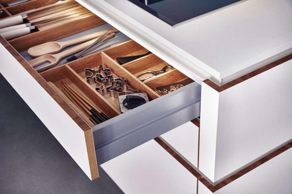 Der Eindruck handwerklicher Perfektion entsteht auch beim Blick ins Innere des neuen Programms Solid. Die Schubla- deneinsätze sind wie die Massivholzkante aus hochwertiger Eiche gefertigt. Foto: LEICHT / P. Schumacher