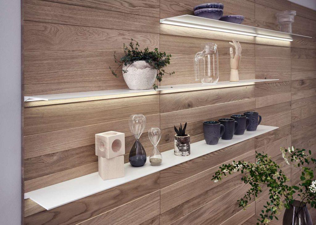 Accessoires geben der Küche eine wohnliche und persön- liche Note: Filigrane Fachborde werden in die hochwertige Paneelwand integriert und individuell positioniert. Foto: LEICHT / P. Schumacher