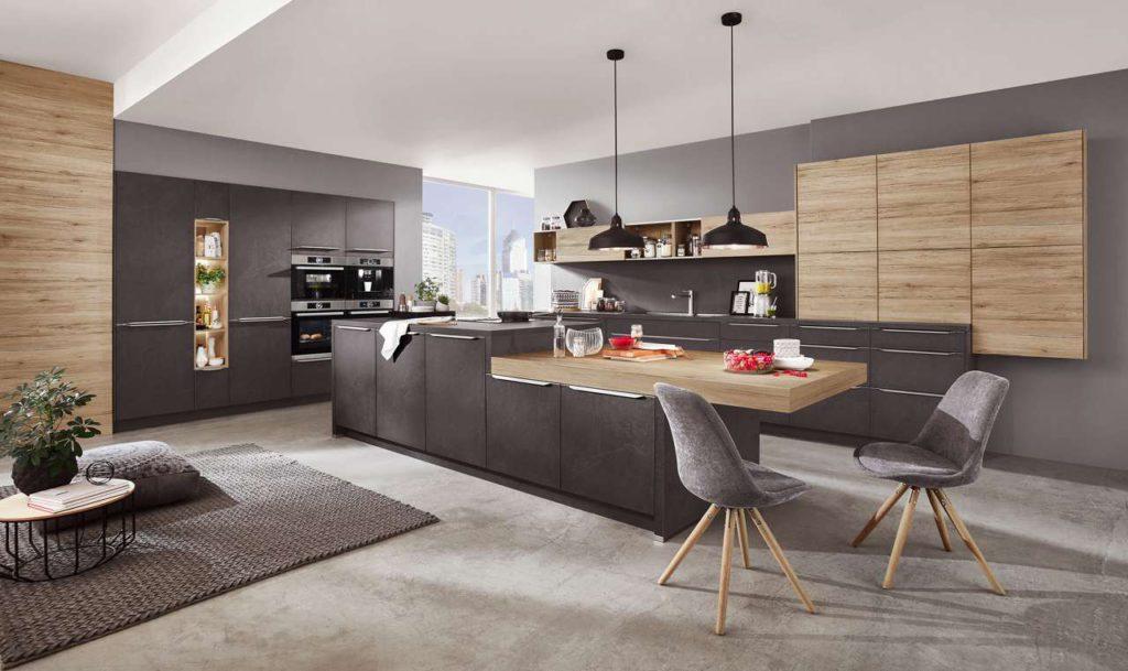 Den Mittelpunkt dieser einladenden Wohnküche bildet eine Kochinsel mit viel Stauraum und einer verlängerten Tischplatte in Eiche-Dekor (Reproduktion). Die schönen dunklen Oberflächen in Grauschiefer-Nachbildung muten mit ihrer 3D-Struktur wie Naturstein an. Foto: AMK