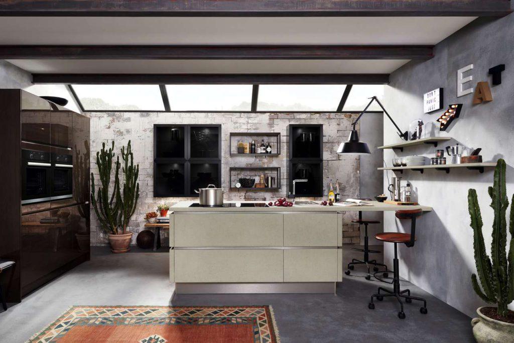 Ihre Attraktivität bezieht diese Wohnküche u. a. auch aus dem eleganten Material- und Farbmix matte Oberflächen in hellem Echtbeton und hochglänzende, mokkafarbene Lackfronten. Foto: AMK