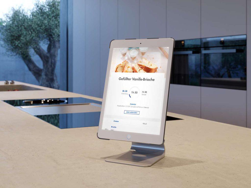 Die Einbaugeräte in den neuen Lifestyle-Wohnküchen sind vernetzt, denn heutzutage wird smart gekocht. Dabei hat man zum Beispiel sein Tablet mit den Schritt-für-Schritt-Anleitungen im Blick. Foto: AMK