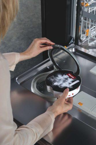 Die PowerDisk lässt sich einfach und schnell in die dafür vorgesehene Vorrichtung an der Türinnenseite einsetzen – und dosiert den Reiniger, indem sie während des Programms automatisch rotiert. <bz/> Foto: Miele