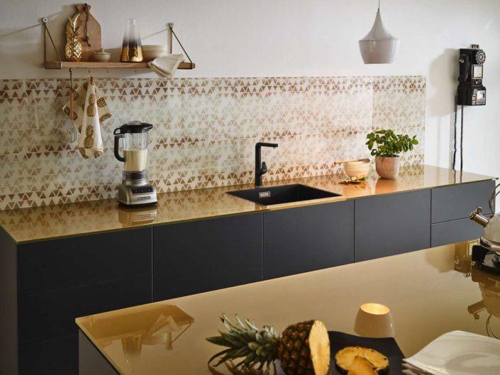Glasarbeitsplatte und bedruckte Rückwand im Golddesign. Foto: Lechner