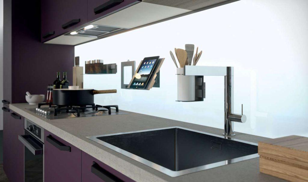 Die beleuchtete Nischenwand aus Glas sieht nicht nur modern aus sondern gibt der Küche auch einen hellen und freundlichen Look. Foto: Aran Küchen