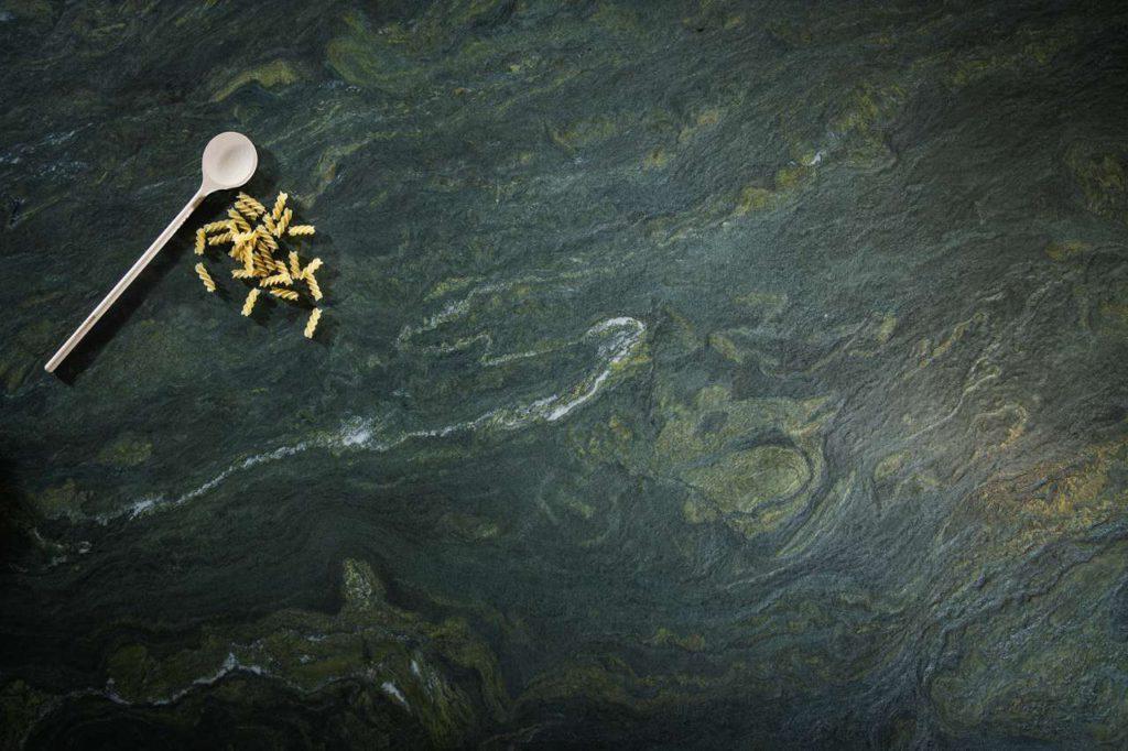 Der olivgrün-gelbe Naturstein wird von dunkelgrauen Schattierungen durchsetzt, schimmert tiefgründig wie ein Gebirgsbach und erfrischt jeden Küchen-Korpus mit Eleganz und natürlichem Charme. Foto: STRASSER Steine