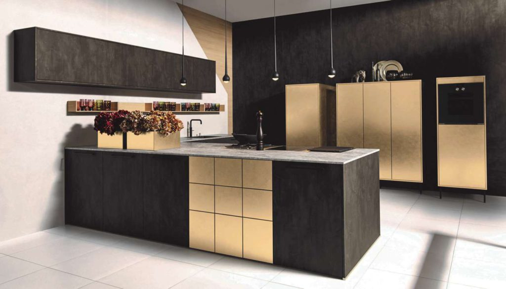 Modulare Eleganz & Ästhetik: Irisierende Metall-Oberflächen sowie dunkle Echthölzer und Holz-Dekore liegen voll im Trend, wie diese attraktive Planung in Metall Gold und dunkler Stahl-Optik zeigt. Foto: AMK