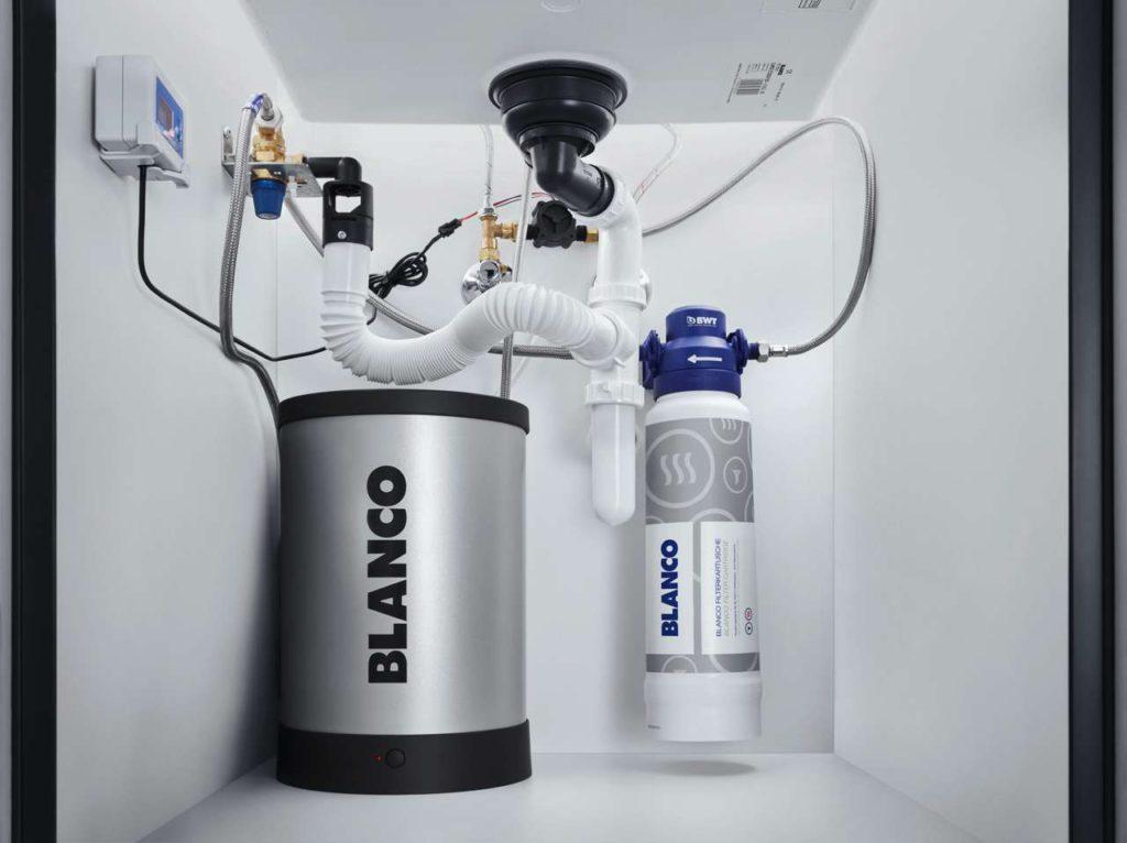 Die Technik für die neue elegante 3-in-1-Armatur Blanco Tampera Hot versteckt sich im Unterschrank. Das höchst komfortable Heißwasser- System lässt sich vom Fachmann auch nachträglich in die Küche einbauen. Foto: Blanco