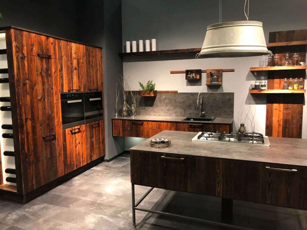 Reduziert auf ein Minimum an Dekor, verbreitet die graphisch strenge AMPEZZO Küche dennoch wohltuende Behaglichkeit durch das warme, rötlichbraun gefärbte Holz antiker Fichte. Foto: Oster Küche