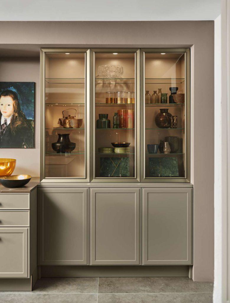 Vitrinentüren mit Rahmen in Manganbronze, dazu bronzefarben getöntes Glas und eine dezente Beleuchtung: Mit abgestimmten Details wie diesen setzt die Neue Klassik auf ein rundum harmonisches Gesamtbild. Foto: Nolte Küchen