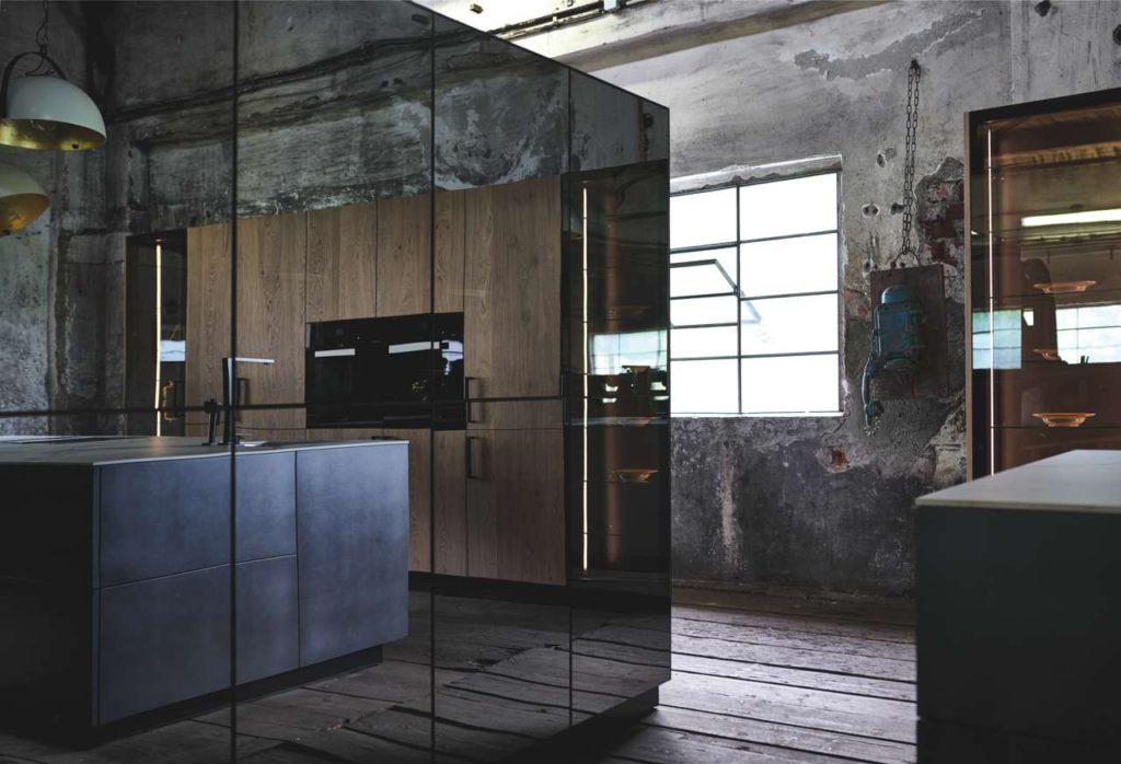 """Schwarze Dekorglasfronten der Fero mit der Kücheninsel in """"dark iron"""" Foto: INTUO"""