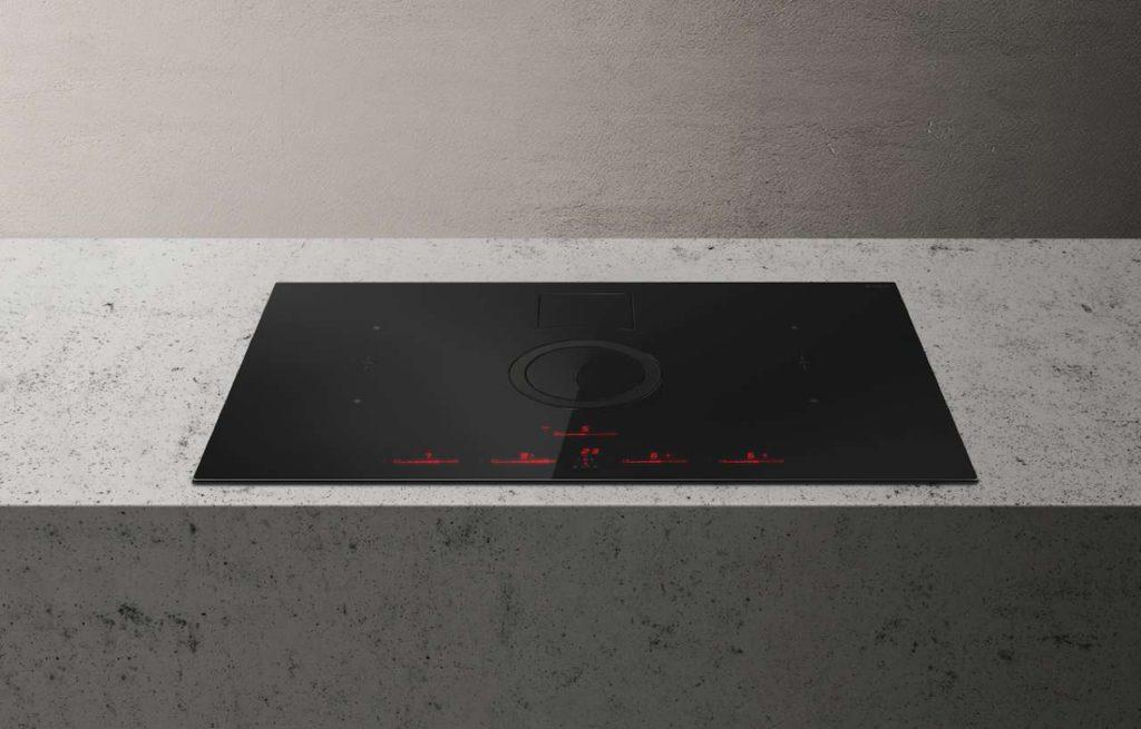 Ab Januar 2019: Schnelle Induktion und sensorgesteuerte Lüftungstechnik – kombiniert in einem Designprodukt. Im Off-Modus ist der runde, flächenbündige Abzug kaum zu entdecken. Um ihn zu aktivieren, einfach leicht draufdrücken. Die runde Klappe stellt sich auf und lässt sich dann in jede gewünschte Richtung drehen, um die Wrasen optimal zu erfassen. Foto: AMK