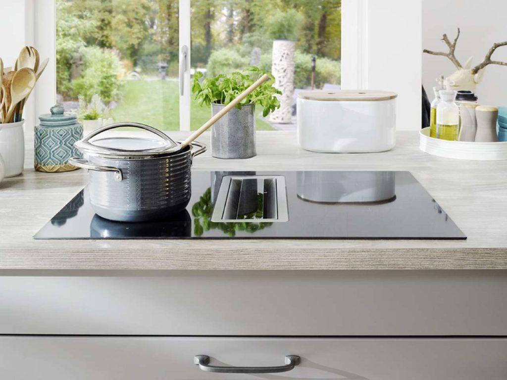 Kompakte Einheit aus Kochfeld und integriertem Abzug, z. B. für Wohnküchen, in denen keine traditionelle Dunstabzugshaube eingesetzt werden soll. Die vier Lüftungsstufen und die Nachlaufautomatik werden über Sensortasten auf dem Kochfeld aktiviert. Foto: AMK