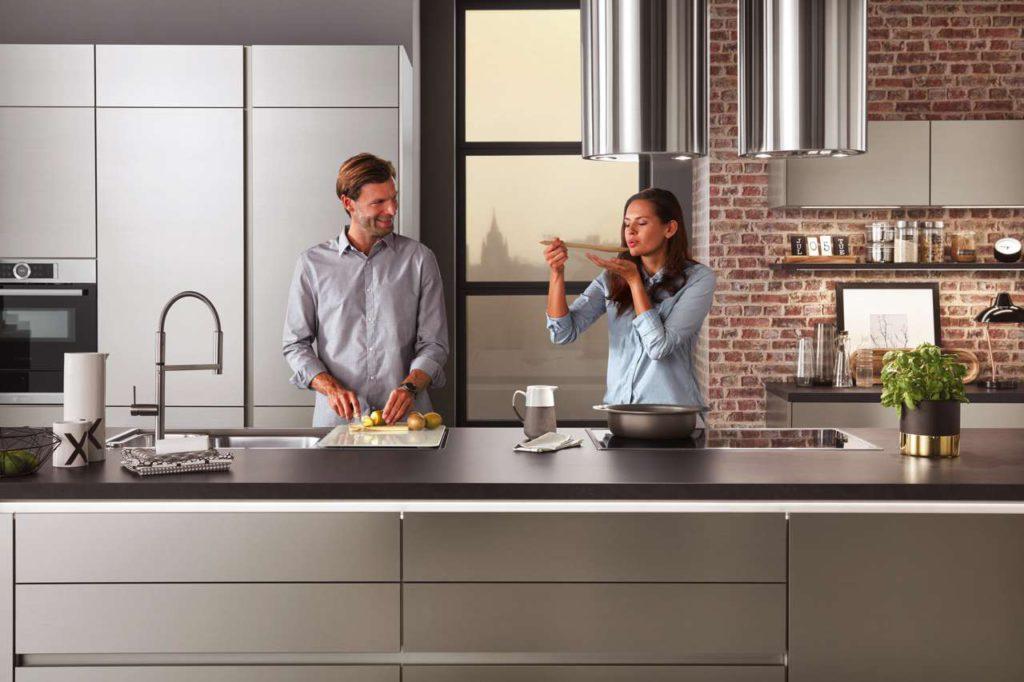 Sind die Personen unterschiedlich groß, können Tischler und Schreiner höhenverstellbare Küchenmöbel für ein rückenschonendes und bequemes Kochen einbauen. Foto: djd/TopaTeam/Nobilia