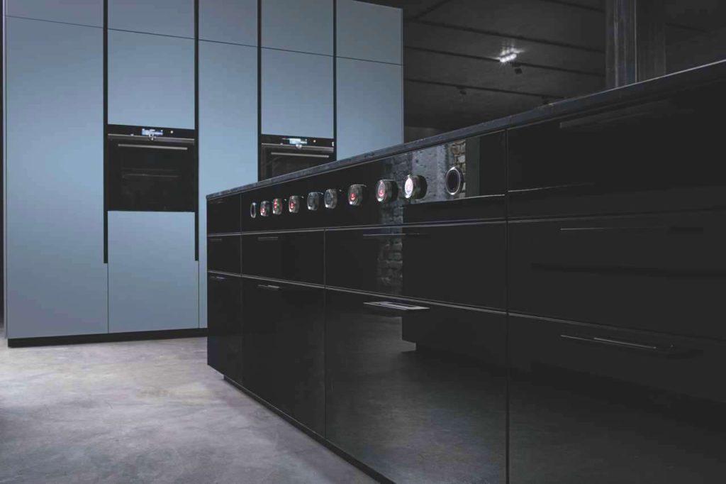 Das Geheimnis der speziellen Ästhetik liegt in dem schwarz lackierten, reflektierenden Dekorglas. Oberschränke und Kücheninsel werden mit ihrer schimmernden Oberfläche und den faszinierenden Spiegelungen zum Blickfang. Foto: ewe