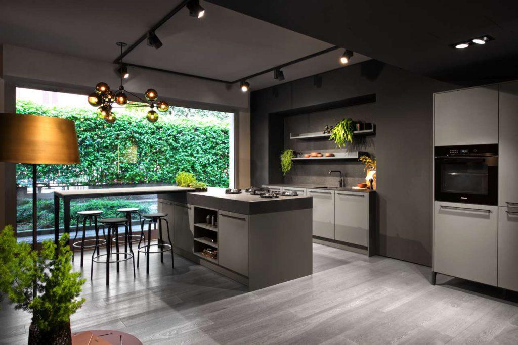 """Die Stilwelt URBAN zeichnet sich durch unkonventionelle, individuelle und solitäre Raumplanungen aus. Die besonderen Merkmale der hier gezeigten Küche sind der neue Farbton """"steingrau"""" in samtmatt mit Antifingerprint-Beschichtung und der in die Arbeitsplatte eingelassene Kräutergarten. Die ungewöhnliche Barlösung greift das Fußgestell des SieMatic Esstisches und der SieMatic 29 auf. Foto: ©SieMatic"""