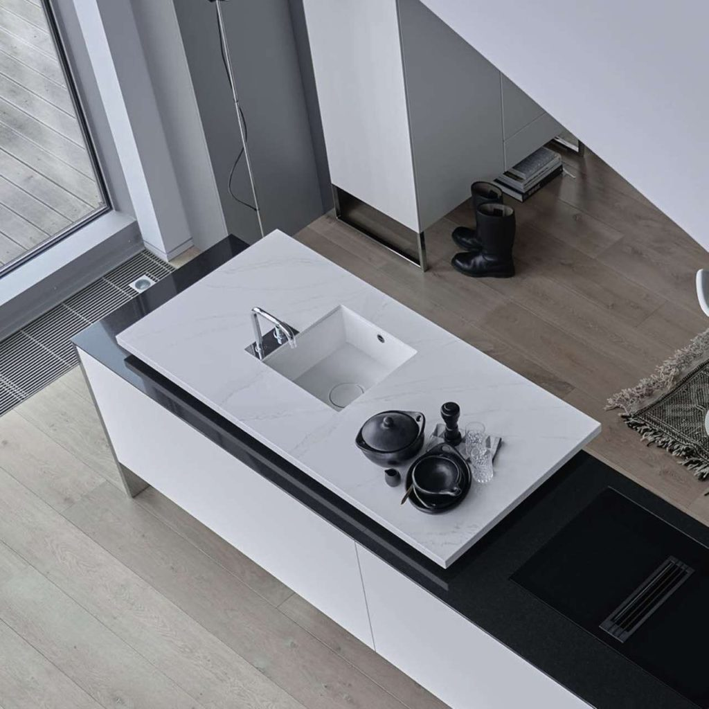 Die Planung dieser neuen, modular konzipierten Designküche setzt auf faszinierende Kontraste in Black and White. Der eleganten weißen Arbeitsfläche mit ihrer hochwertigen Optik machen weder Hitze noch scharfe Gegenstände etwas aus. Foto: AMK
